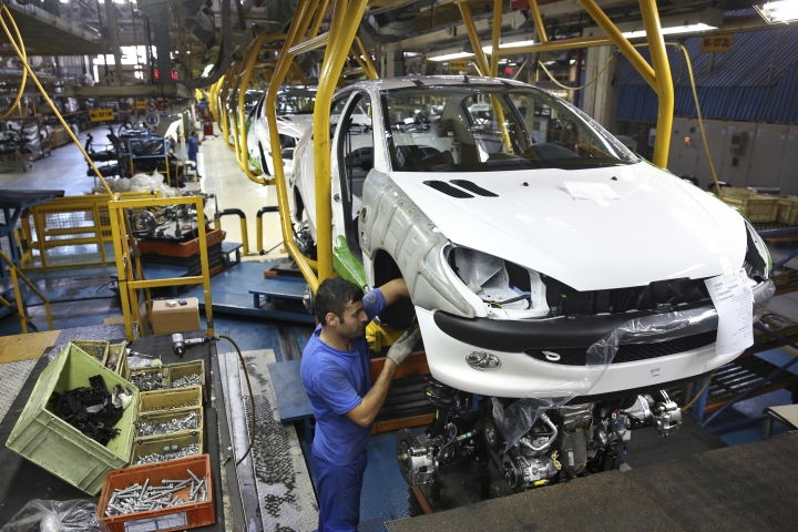 FILE - In this Oct. 11, 2014 file photo, an Iranian worker assembles a Peugeot 206 at the state-run Iran-Khodro automobile manufacturing plant near Tehran, Iran. From brand-new airplanes to oilfields, billions of dollars of deals stand on the line for international corporations as President Donald Trump weighs whether to pull America out of Iran's nuclear deal with world powers. (AP Photo/Ebrahim Noroozi, File)