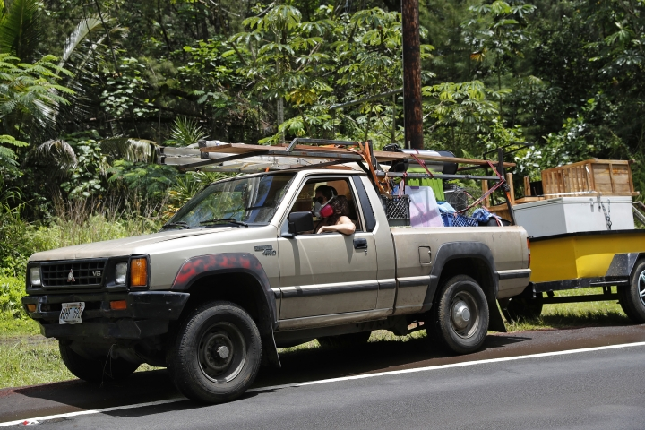 While wearing an air filter mask, Laura Dawn drives her truck loaded with her possessions as she and her husband flee the lava eruption, Sunday, May 6, 2018, near Pahoa, HI. Their property is just below the active lava eruption and they fear their land will get covered in lava. They are moving further upcoast to a safer area. (AP Photo/Marco Garcia)