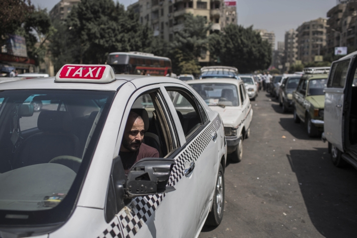 FILE - In this Sept. 4 2014 file photo, a taxi driver waits in line for fuel at a gas station in Cairo's neighboring city of Giza, Egypt. Egypt's parliament approved a law to govern popular ride-hailing apps Uber and Careem, which had faced legal challenges. The new law, as described Monday, May 7, 2018, by state news agency MENA, establishes operating licenses and fees. It requires licensed companies to store user data for 180 days and provide it to Egyptian security authorities upon request. (AP Photo/Eman Helal, File)