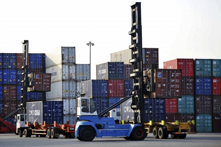 Workers move containers at a port in Qingdao in eastern China's Shandong province Tuesday, May 8, 2018. Official figures show that China's exports expanded by 21.5 percent in April, bouncing back from a contraction the previous month, in a sign of resurgent global demand.(Chinatopix Via AP) CHINA OUT