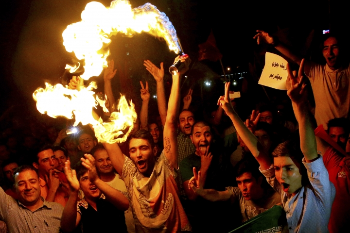 FILE - In this July 14, 2015 file photo, Iranians celebrate following a landmark nuclear deal in Tehran, Iran. Iran's nuclear deal with world powers faces its biggest diplomatic challenge yet as President Donald Trump appears poised to withdraw the U.S. from the accord. (AP Photo/Ebrahim Noroozi, File)