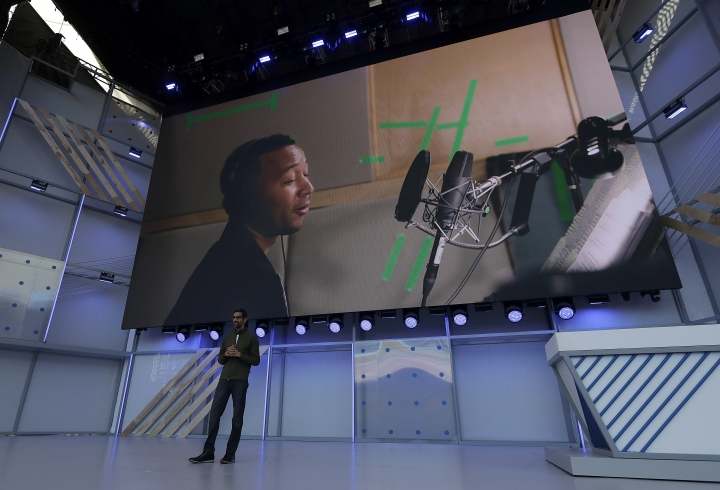 Google CEO Sundar Pichai speaks under a video showing singer John Legend at the Google I/O conference in Mountain View, Calif., Tuesday, May 8, 2018. (AP Photo/Jeff Chiu)