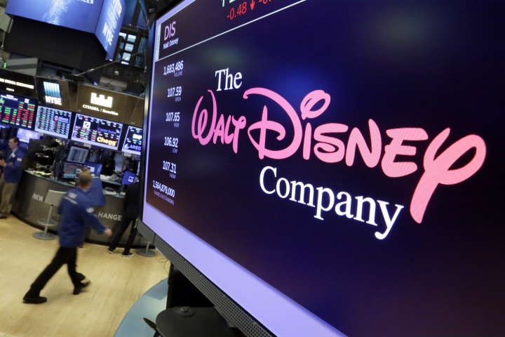FILE - In this Monday, Aug. 7, 2017, file photo, The Walt Disney Co. logo appears on a screen above the floor of the New York Stock Exchange. Disney is seeking new frontiers. The media company launched its $5-a-month sports streaming service, ESPN Plus, in April 2018, and it signed a deal with Twitter a month later to create Marvel, ABC and ESPN content on that service. Meanwhile, Disney is trying to buy much of 21st Century Fox, including the Fox television network and the X-Men movie franchise. (AP Photo/Richard Drew, File)