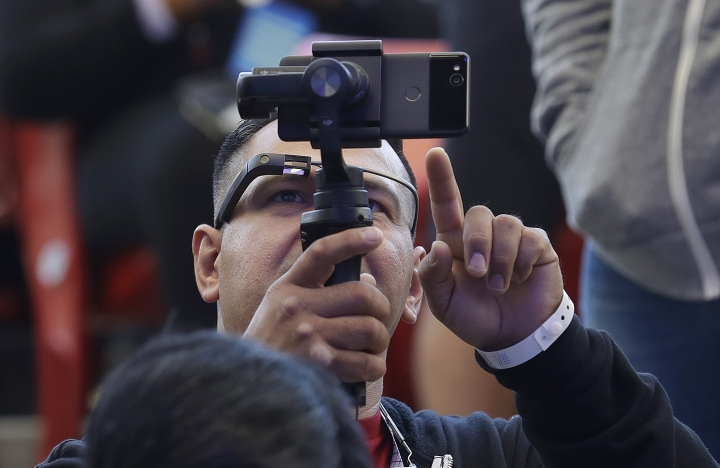 Developer Jesus Suarez wears Google Glass glasses while looking at his phone before the start of the keynote address at the Google I/O conference in Mountain View, Calif., Tuesday, May 8, 2018. (AP Photo/Jeff Chiu)