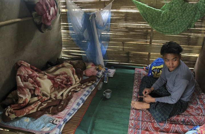 In this May 6, 2018, photo, ethnic Kachin Mung San, right, sits near his father Gam Awng who is suffering TB, at their hut in compound of Trinity Baptist Church refugee camp for internally displaced people in Myitkyina, Kachin State, northern Myanmar. Myanmar's army, notorious for perpetrating violence that drove 700,000 Muslim ethnic Rohingyas to flee to neighboring Bangladesh, now stands accused of fostering a similar humanitarian crisis in the country's north, where it battles guerrillas of the Christian Kachin minority. (AP Photo/Min Kyi Thein)