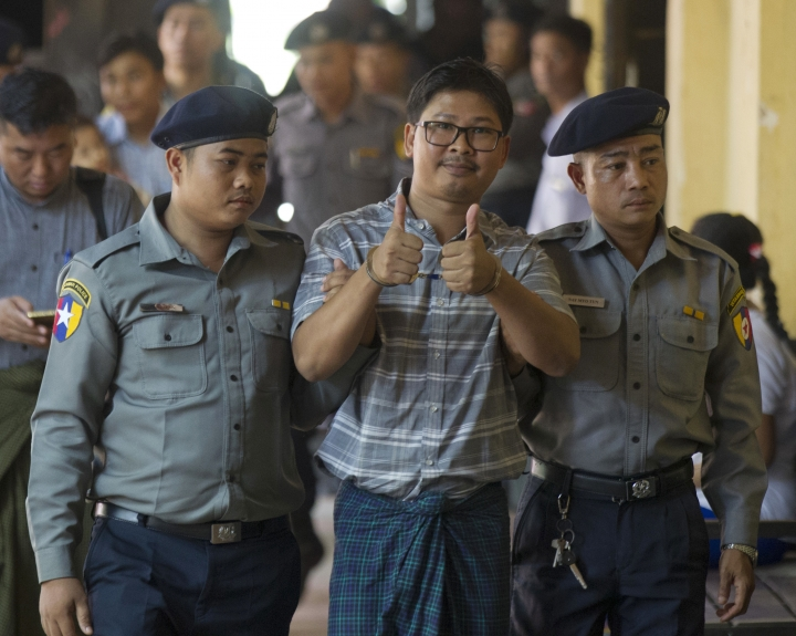 Reuters journalist Wa Lone, center, thumbs up as he is escorted by police upon arrival for trial in Yangon, Myanmar Wednesday, May 9, 2018. Two Reuters journalists accused of being in possession of restricted papers under the Official Secrets Act, return to court as their trial resumes. (AP Photo/Thein Zaw)