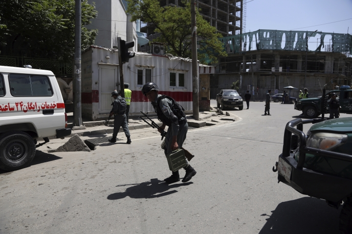 Afghan security personnel inspect at the site of a suicide attack in the center of Kabul, Afghanistan, Wednesday, May 9, 2018. Three suicide bombers struck two police stations in Afghanistan's capital on Wednesday, wounding at least six people, officials said. (AP Photo/Rahmat Gul)