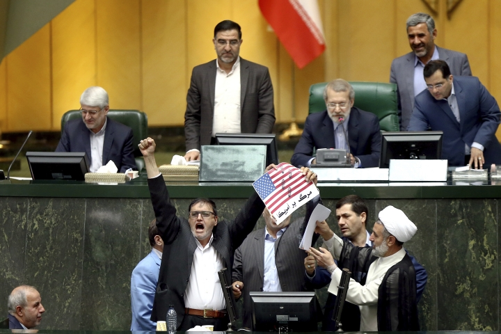 "Iranian lawmakers prepare to burn two pieces of papers representing the U.S. flag and the nuclear deal as they chant slogans against the U.S. at the parliament in Tehran, Iran, Wednesday, May 9, 2018. Iranian lawmakers have set a paper U.S. flag ablaze at parliament after President Donald Trump's nuclear deal pullout, shouting, ""Death to America!"". President Donald Trump withdrew the U.S. from the deal on Tuesday and restored harsh sanctions against Iran. (AP Photo)"
