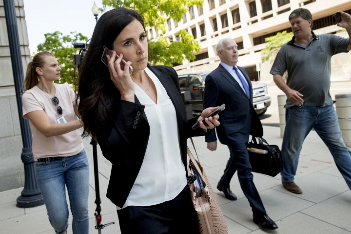 Attorneys Eric Dubelier, second from right, and Katherine Seikaly, second from left, representing Concord Management and Consulting LLC, walk out of federal court in Washington, Wednesday, May 9, 2018, after pleading not guilty on behalf of the company, which has been charged as part of a conspiracy to meddle in the 2016 US presidential election. (AP Photo/Andrew Harnik)