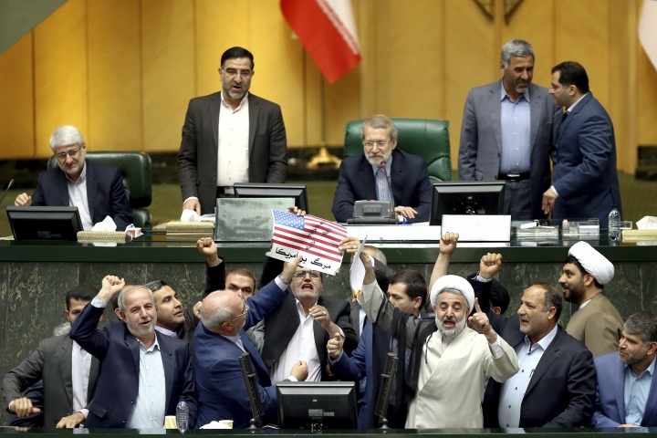 """Iranian lawmakers burn two pieces of papers representing the U.S. flag and the nuclear deal as they chant slogans against the U.S. at the parliament in Tehran, Iran, Wednesday, May 9, 2018. Iranian lawmakers have set a paper U.S. flag ablaze at parliament after President Donald Trump's nuclear deal pullout, shouting, """"Death to America!"""". Trump withdrew the U.S. from the deal on Tuesday and restored harsh sanctions against Iran. (AP Photo)"""
