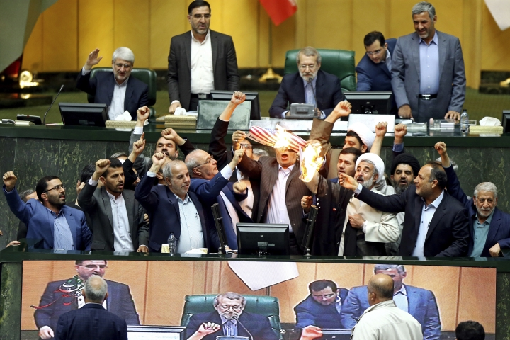 "Iranian lawmakers burn two pieces of papers representing the U.S. flag and the nuclear deal as they chant slogans against the U.S. at the parliament in Tehran, Iran, Wednesday, May 9, 2018. Iranian lawmakers have set a paper U.S. flag ablaze at parliament after President Donald Trump's nuclear deal pullout, shouting, ""Death to America!"". President Donald Trump withdrew the U.S. from the deal on Tuesday and restored harsh sanctions against Iran. (AP Photo)"