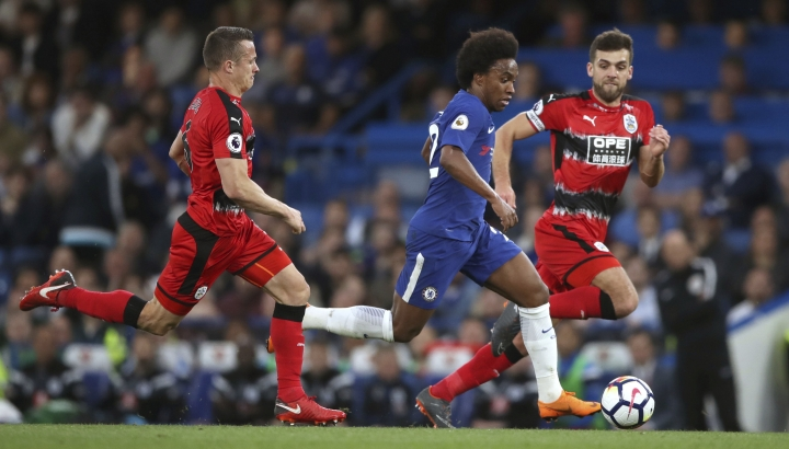Chelsea's Willian runs past Huddersfield Town's Jonathan Hogg, left, and Tommy Smith during the English Premier League soccer match at Stamford Bridge, London, Wednesday May 9, 2018. (John Walton/PA via AP)