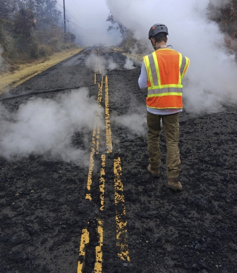 In this photo provided by the U.S. Geological Survey, a geologist walks along center lane lines that have been offset by fissuring on Leilani Street in Leilani Estates near the town of Pahoa, Hawaii, Wednesday, May 9, 2018. Geologists warned Wednesday that Hawaii's Kilauea volcano could erupt explosively and send boulders, rocks and ash into the air around its summit in the coming weeks. (U.S. Geological Survey via AP)