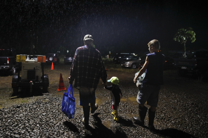 "Evacuee Jon Warner, left, walks through rain with son Ethan, right, and daughter Iris after picking up some basic necessities at a makeshift donation center Tuesday, May 8, 2018, in Pahoa, Hawaii. ""We've never seen anything like that before,"" said Warner. ""I don't know if I ever want to go back."" (AP Photo/Jae C. Hong)"