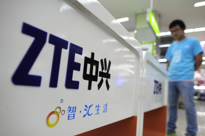 FILE - In this Oct. 8, 2012, file photo, a salesperson stands at counters selling mobile phones produced by ZTE Corp. at an appliance store in Wuhan in central China's Hubei province. The tech company, ZTE, a Chinese tech giant brought to its knees and delayed shipments of imported U.S. cars, apples, lumber and other agricultural products are the early casualties as China and the U.S. exchange salvos in a trade dispute.(Chinatopix Via AP, File)