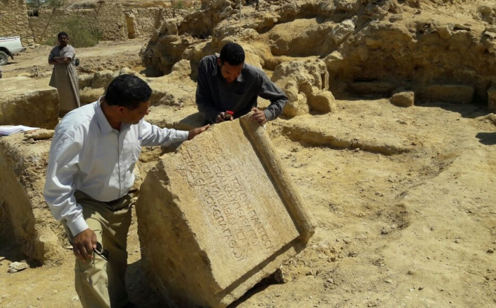 This undated photo released by the Egyptian Ministry of Antiquities, shows archaeologists examining an ancient stone found among the remains of a temple dating back to the second century, in the country's western desert, some 50 km west of Siwa Oasis, Egypt. The ministry said Thursday, May 10, 2018, that the temple, dates back to the reign of Roman Emperor Antoninus Pius. (Egyptian Ministry of Antiquities via AP)