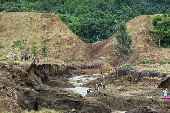 People gather in front of the broken banks of the Patel dam near Solai, in Kenya's Rift Valley, Thursday, May 10, 2018. A dam burst its banks in Kenya's Rift Valley, killing at least 41 people and forcing hundreds from their homes, officials said Thursday. At least 20 of the dead were children, police said. (AP Photo)