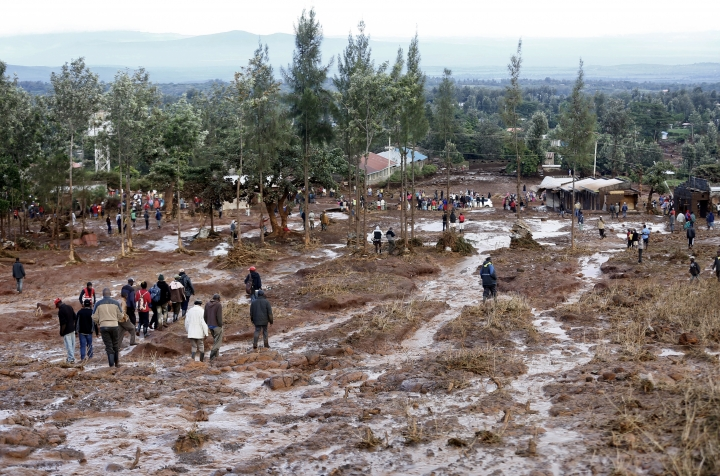 People walk through an area swept away by waters from the Patel dam near Solai, in Kenya's Rift Valley, Thursday, May 10, 2018. A dam burst its banks in Kenya's Rift Valley, killing at least 41 people and forcing hundreds from their homes, officials said Thursday. At least 20 of the dead were children, police said. (AP Photo)