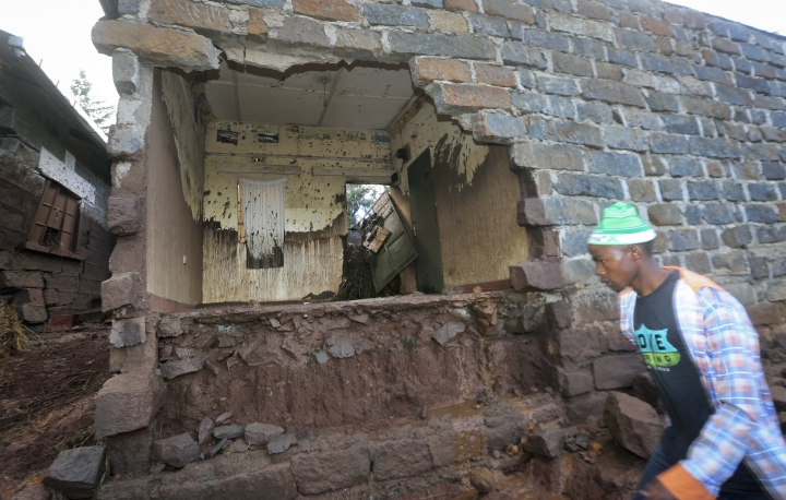 A man walks past a house damaged by flooding, near Solai, in Kenya's Rift Valley, Thursday, May 10, 2018. A dam burst its banks in Kenya's Rift Valley, killing at least 41 people and forcing hundreds from their homes, officials said Thursday. At least 20 of the dead were children, police said. (AP Photo)