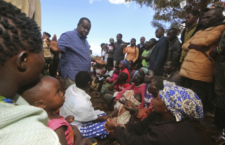 Survivors of the flooding huddle together in Kenya's Rift Valley, near Solai, Thursday, May 10, 2018. A dam burst its banks in Kenya's Rift Valley, killing at least 41 people and forcing hundreds from their homes, officials said Thursday. At least 20 of the dead were children, police said. (AP Photo)
