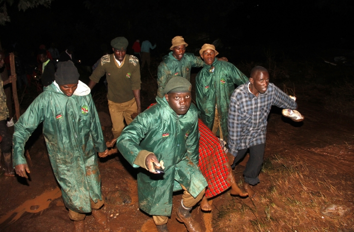 Members of the National Youth Service carry away a dead body covered in a blanket during the early hours of Thursday, May 10, 2018 near Solai, in Kenya's Rift Valley. Water burst through the banks of the Patel Dam in Nakuru County late Wednesday night after heavy rains, sweeping away hundreds of homes and killing dozens. (AP Photo)