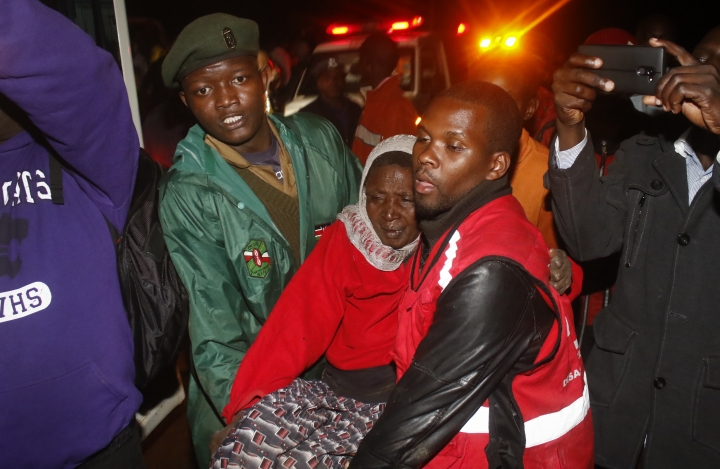 A paramedic carries an injured woman during the early hours of Thursday, May 10, 2018, near Solai, in Kenya's Rift Valley. Water burst through the banks of the Patel Dam in Nakuru County late Wednesday night after heavy rains, sweeping away hundreds of homes and killing dozens. (AP Photo)