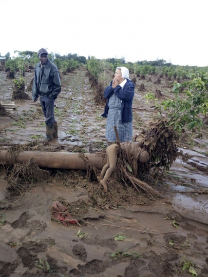 EDS NOTE GRAPHIC CONTENT : A nun reacts as she stands near the dead body of a child covered in mud, while a local resident looks on, at the scene of deadly floods near Solai, in Kenya's Rift Valley, Thursday, May 10, 2018. The Patel Dam burst its banks late Wednesday night after heavy rains, sweeping away hundreds of homes and killing some dozens, many of them children. (AP Photo)