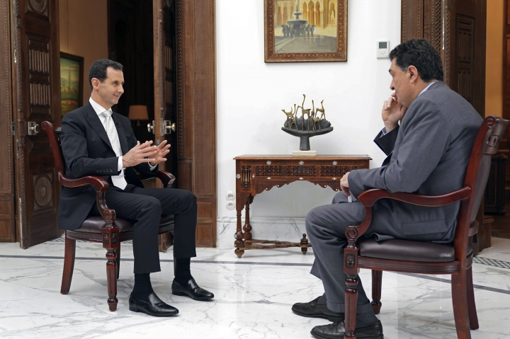 In this photo released Thursday, May 10, 2018, by the Syrian official news agency SANA, Syrian President Bashar Assad speaks during an interview with Alexis Papachelas, the the executive editor of the Greek Kathimerini newspaper, in Damascus, Syria. In the interview published Thursday, Assad said the current U.S. administration is inconsistent and nothing can be achieved with it in terms of ending the raging conflict in his country and that he hoped there is no direct confrontation between the U.S and Russia in Syria. (SANA via AP)