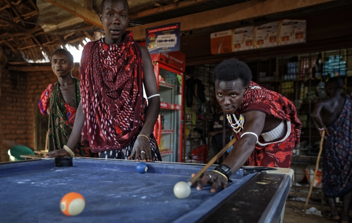 FILE - In this Friday, March 23, 2018 file photo, young Maasai men relax and play a game of pool at a bar by the side of the road in the late afternoon at Mkata junction, near Mikumi National Park in Tanzania. A U.S.-based group said Thursday, May 10, 2018 that tens of thousands of Tanzania's ethnic Maasai people have been left homeless after their houses were burned to keep the savannah open for tourism benefiting foreign safari companies. (AP Photo/Ben Curtis, File)
