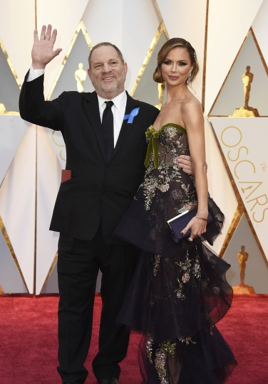 """FILE - In this Feb. 26, 2017 file photo, producer Harvey Weinstein, left, and fashion designer Georgina Chapman arrive at the Oscars in Los Angeles. Chapman, Weinstein's estranged wife, has given a tearful interview in Vogue magazine which she says she never knew of her husband's misconduct. The interview comes a day after Wintour came out in support of Chapman on Stephen Colbert's late-night show, """"Late Night with Stephen Colbert"""" and a few days after Scarlett Johansson wore a gown by Marchesa, Chapman's fashion line, at the Met Gala. (Photo by Jordan Strauss/Invision/AP, File)"""
