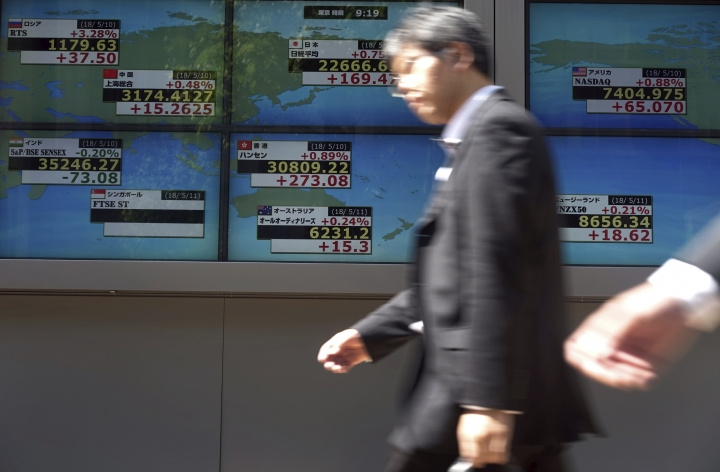 A man walks past an electronic stock board showing Japan's Nikkei 225 index and other country's index at a securities firm in Tokyo Friday, May 11, 2018. Asian stock markets rallied on Friday, tracing gains on Wall Street after weaker than expected inflation figures soothed concerns about a possible acceleration of interest rate hikes. Oil prices were hovering at a fresh multiyear high. (AP Photo/Eugene Hoshiko)