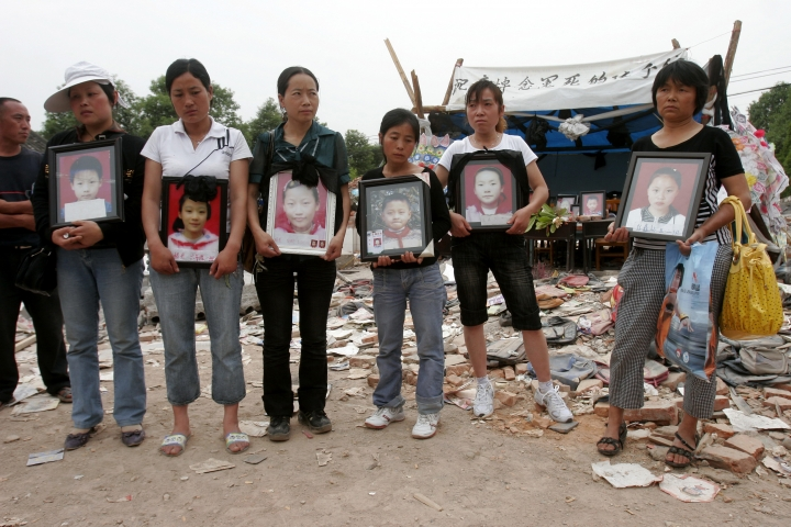 In this May 28, 2008, photo, women hold portraits of some of the 127 students of Fuxin No. 2 Elementary School killed when their school collapsed during an earthquake in Mianzhu in southwest China's Sichuan province. Ten years after a massive earthquake devastated parts of China's Sichuan province, outspoken critic of the government's disaster response Huang Qi is languishing in prison awaiting trial amid deteriorating health. The longtime human rights advocate's predicament underscores the communist government's determination to silence all critics, including parents who lost their children when shoddily built schools collapsed in 2008. (Chinatopix via AP)