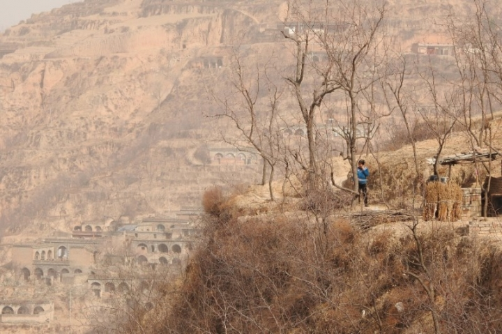 Villager Guo Jiaming, 70, stands outside her cave dwelling on a mountain cliffside in Lin county, Shanxi province, China March 15, 2018. REUTERS/Joseph Campbell