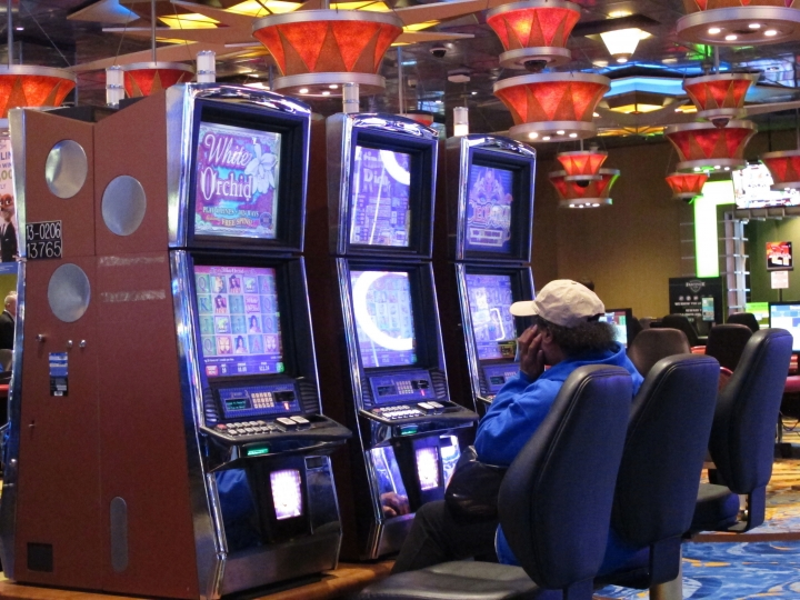 This April 20, 2018 photo shows a woman playing slot machines at Resorts Casino Hotel in Atlantic City, N.J. As Atlantic City's casinos mark their 40th anniversary, the industry is hailing the reopening of two of the five casinos that shut down since 2014. But some worry that re-expanding the market could lead to the same conditions that caused the wave of closings in the first place. (AP Photo/Wayne Parry)