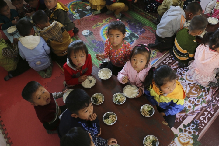 In this May 9, 2018 photo provided by the World Food Program (WFP), children eat a meal at a nursery and kindergarten where WFP provides food assistance in Sinwon county in North Korea's South Hwanghae province. The head of the United Nations' World Food Program says a peace agreement with North Korea will go far toward easing the impoverished nation's chronic food security woes. (Silke Buhr/World Food Program via AP)