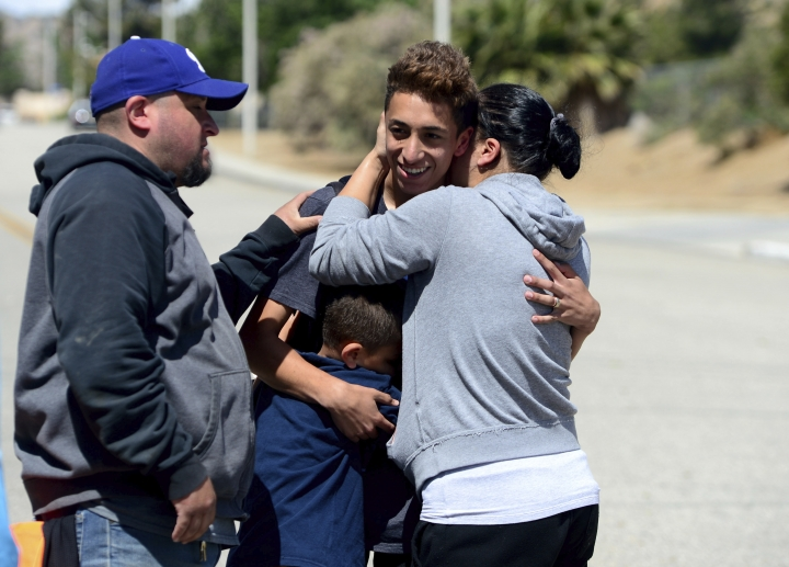 Jennifer Monpano hugs her son Ruben Murillo-Villa, 16, as the family was reunited outside Highland High School in Palmdale after Sheriff took the school off lockdown on Friday, May 11, 2018. A 14-year-old used a rifle to shoot a classmate in the arm Friday at their high school in California and dumped the gun in the desert before he was caught in a shopping center, authorities said. (Dean Musgrove/Los Angeles Daily News/SCNG via AP)