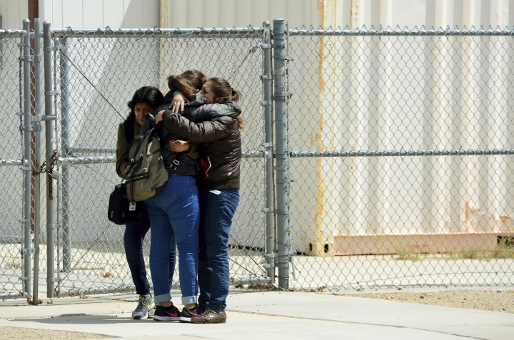 Victoria Aquino hugs her two daughters, Melany, 17 and Halie, 11, as the family was reunited outside Highland High School in Palmdale, Calif., after the sheriff took the school off lockdown following a shooting, on Friday, May 11, 2018. (Dean Musgrove/Los Angeles Daily News/SCNG via AP)