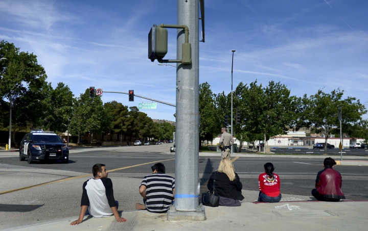 Students wait on a curb outside Highland High School in Palmdale, Calif. as Sheriff search the school on Friday, May 11, 2018. A high school student was shot in the arm Friday at high school in the California city of Palmdale and a 14-year-old suspect was taken into custody, officials said. (Dean Musgrove /Los Angeles Daily News via AP)