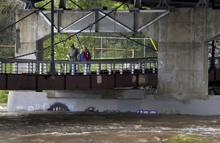 A pair of pedestrians cross the Madison Street footbridge over the Clark Fork River in downtown Missoula, Montana, Friday, May 11, 2018. The river was expected to crest more than a foot above major flood stage late Saturday — its highest level in 100 years. Montana authorities warned of dangerous debris being swept downstream as water levels continued rising Friday in rivers and streams across the western half of the state. (Kurt Wilson/The Missoulian via AP)