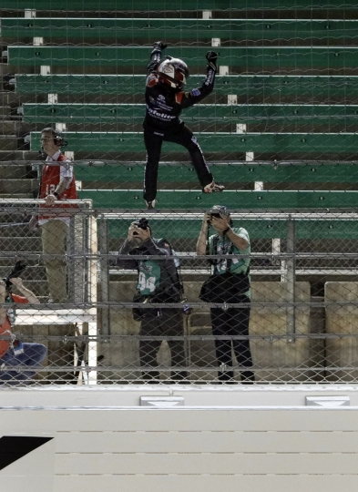Noah Gragson celebrates by climbing the catch fence after winning the NASCAR Truck Series auto race at Kansas Speedway in Kansas City, Kan., Friday, May 11, 2018. (AP Photo/Orlin Wagner)