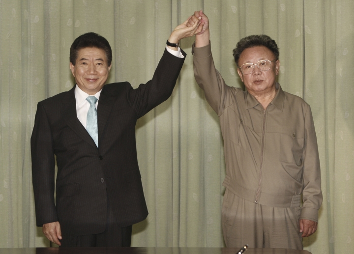 """FILE - In this Oct. 4, 2007, file photo, then South Korean President Roh Moo-hyun, left, holds hands with then North Korean leader Kim Jong Il after exchanging a joint declaration documents in Pyongyang, North Korea. Current South Korean President Moon Jae-in, the son of North Korean war refugees, has vowed to build on the legacies of late liberal Presidents Kim Dae-jung and Roh Moo-hyun and their so-called """"Sunshine Policy,"""" which Moon had a hand in building. (Pool Photo via AP, File)"""