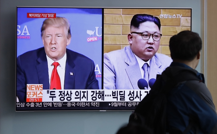 """FILE - In this May 11, 2018, file photo, a man watches a TV screen showing file footage of U.S. President Donald Trump, left, and North Korean leader Kim Jong Un during a news program at the Seoul Railway Station in Seoul, South Korea. The outcome of South Korean President Moon Jae-in's efforts may hinge on a meeting in Singapore in June between Kim and Trump, who spent months contemplating military strikes against the North before Moon steered him to the table. The letters read """"Summit between U.S. and North Korea, Forecast, Clear."""" (AP Photo/Lee Jin-man)"""