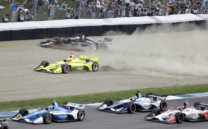 Jordan King, top, of England, and Simon Pagenaud, of France, are forced into the gravel at the start of the IndyCar Grand Prix auto race at Indianapolis Motor Speedway, in Indianapolis Saturday, May 12, 2018. (AP Photo/Darron Cummings)