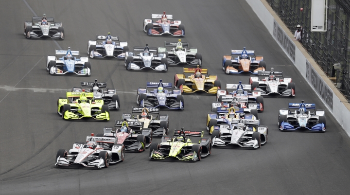 Will Power, left, of Australia, leads the field into tune one at the start of the IndyCar Grand Prix auto race at Indianapolis Motor Speedway, in Indianapolis Saturday, May 12, 2018. (AP Photo/Darron Cummings)