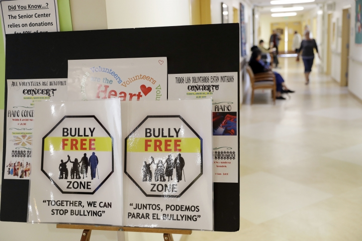 In this Friday, April 13, 2018 photo, signs promote a bully-free environment at the On Lok 30th Street Senior Center in San Francisco. After problems at the facility, all staff members received 18 hours of training that included lessons on what constitutes bullying, causes of the problem and how to manage such conflicts. Seniors were then invited to similar classes teaching them to alert staff or intervene themselves if they witness bullying. (AP Photo/Marcio Jose Sanchez)