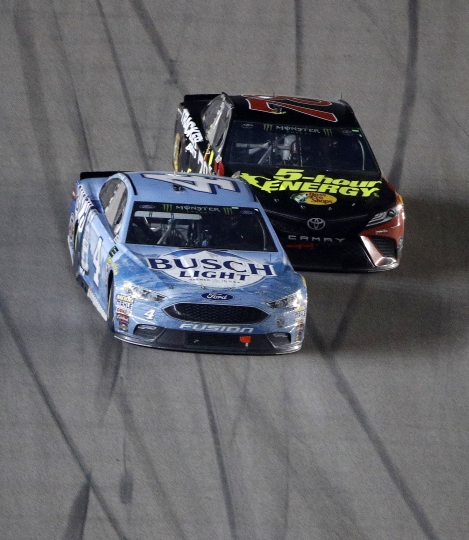 Kevin Harvick (4) passes Martin Truex Jr. (78) with a lap to go to win the NASCAR Cup Series auto race at Kansas Speedway on Saturday, May 12, 2018, in Kansas City, Kan. (AP Photo/Charlie Riedel)