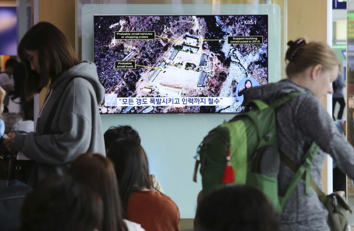 """A TV screen shows a satellite image of the Punggye-ri nuclear test site in North Korea during a news program at the Seoul Railway Station in Seoul, South Korea, Sunday, May 13, 2018. North Korea said Saturday that it will dismantle its nuclear test site in less than two weeks, in a dramatic event that would set up leader Kim Jong Un's summit with President Donald Trump next month. Trump welcomed the """"gracious gesture."""" The signs read: """"Explode all tunnels."""" (AP Photo/Ahn Young-joon)"""