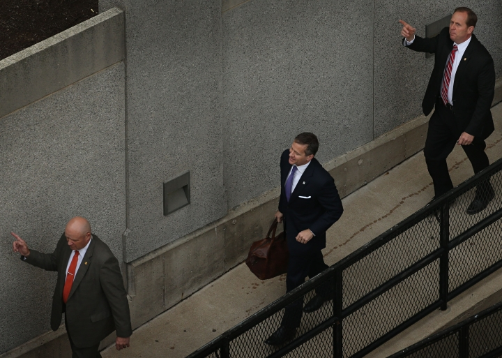 In this May 10, 2018, photo, flanked by security guards, Missouri Gov. Eric Greitens, center, arrives at court for jury selection in his felony invasion of privacy trial, in St. Louis. In spring 2015, Missouri Gov. Eric Greitens was launching a political career, a new book and an extramarital affair. That spring has now grown into a mountain of trouble. He goes to trial this week on an invasion-of-privacy charge stemming from the affair. He also faces a felony charge for using a charity donor list to raise money for his campaign. And a university is reviewing his use of grant funds for his book. (David Carson/St. Louis Post-Dispatch via AP)
