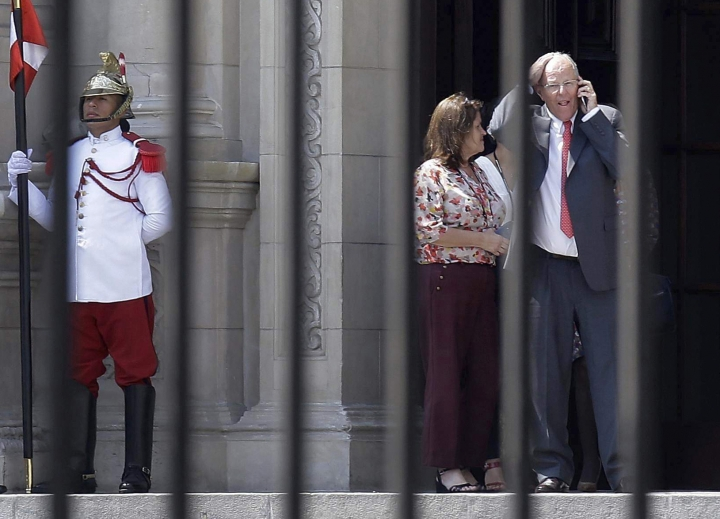 FILE - In this March 21, 2018 file photo, Peru's President Pedro Pablo Kuczynski talks on his cellphone as he vacates the House of Pizarro, the presidential residence and workplace, in Lima, Peru. Kuczynski resigned amid allegations that the Brazilian construction giant Odebrecht paid his consulting firm $780,000 a decade ago. Kuczynski denies wrongdoing. (AP Photo/Martin Mejia, File)