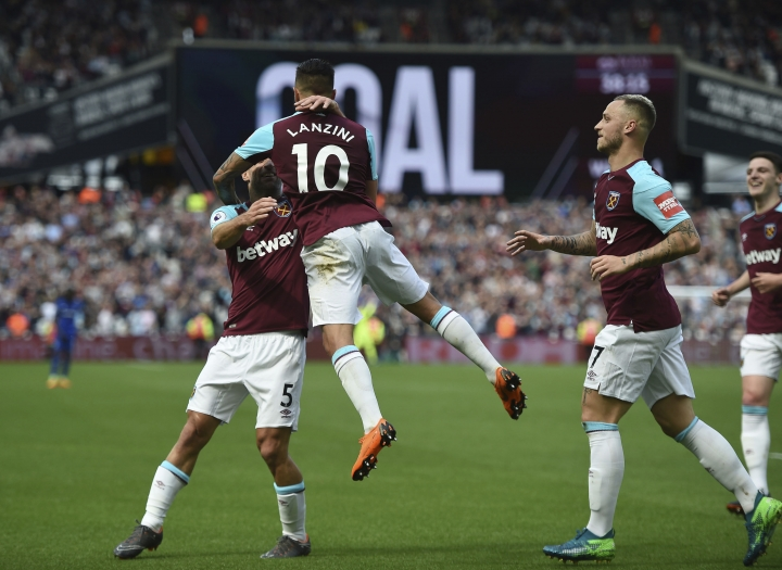 West Ham United's Manuel Lanzini, centre, celebrates scoring his side's first goal of the game with teammate Pablo Zabaletae during the English Premier League soccer match between West Ham United and Everton, at the London Stadium, in London, Sunday May 13, 2018. (Daniel Hambury/PA via AP)